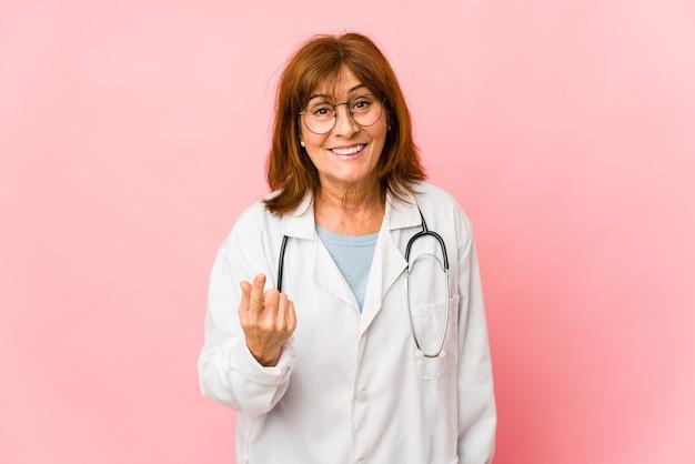 La donna caucasica del medico di mezza età isolata che indica con il dito contro di voi come se invitando si avvicini.