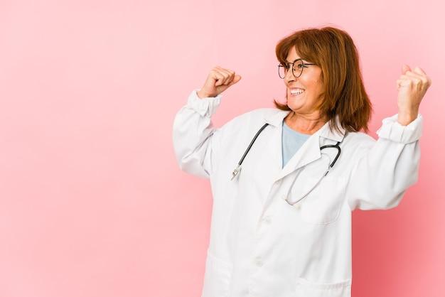 La donna caucasica del medico di mezza età ha isolato il pugno di sollevamento dopo una vittoria, concetto del vincitore.
