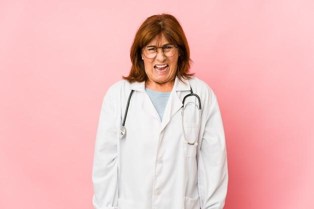 Donna caucasica di medico di mezza età isolata che grida molto arrabbiata e aggressiva.