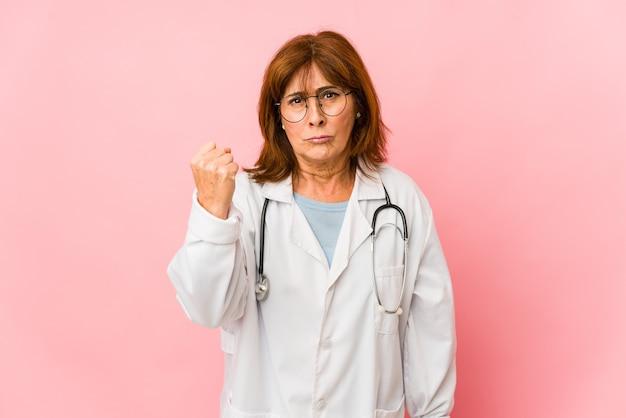 La donna caucasica del medico di mezza età ha isolato il pugno che mostra alla macchina fotografica, l'espressione facciale aggressiva.
