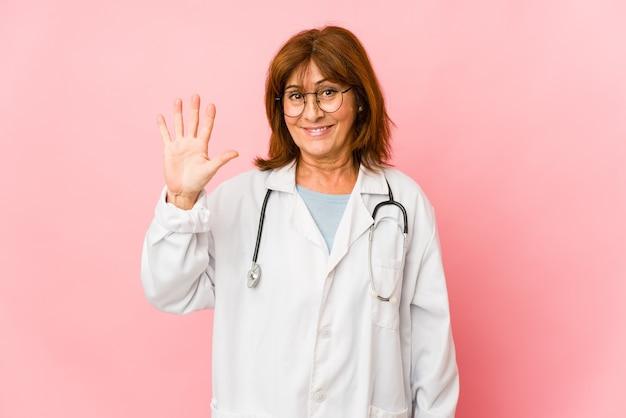 La mezza età caucasica medico donna isolata sorridente allegro che mostra il numero cinque con le dita.