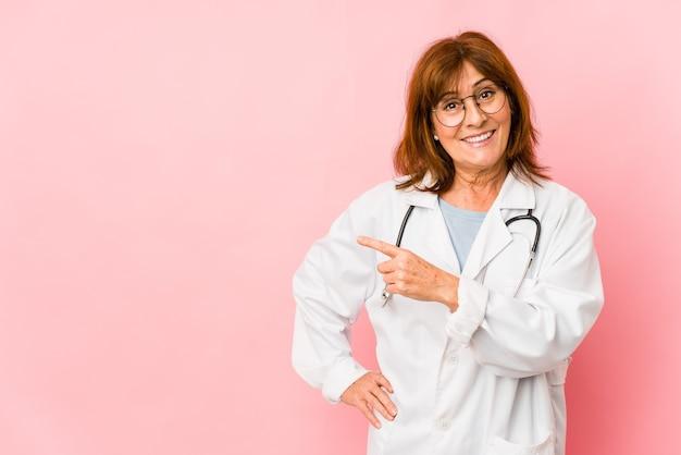 La donna caucasica di medico di mezza età isolata sorridendo e indicando da parte, mostrando qualcosa nello spazio vuoto
