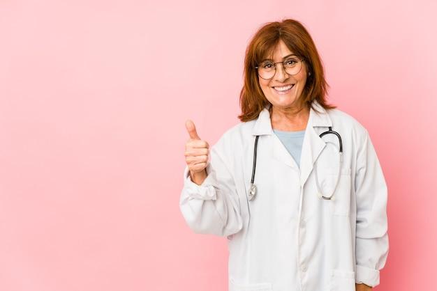 La donna caucasica di medico di mezza età isolata sorridendo e alzando il pollice in su