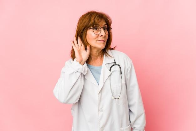 Donna caucasica di medico di mezza età isolata che prova ad ascoltare un pettegolezzo.
