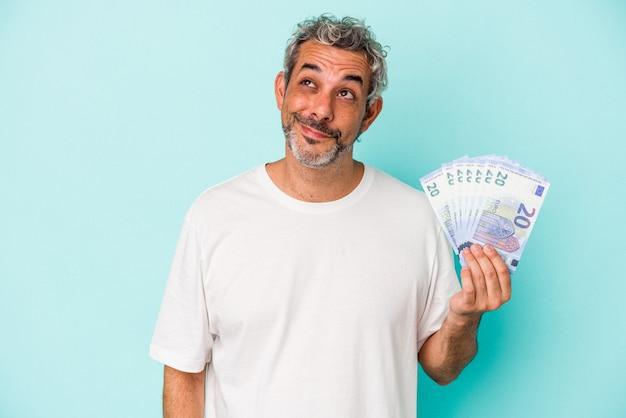 Uomo caucasico di mezza età che tiene banconote isolate su sfondo blu sognando di raggiungere obiettivi e scopi