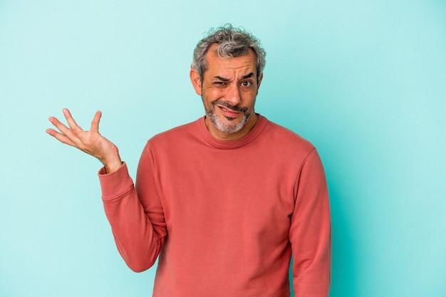 Uomo caucasico di mezza età isolato su sfondo blu dubitando e alzando le spalle nel gesto interrogativo.