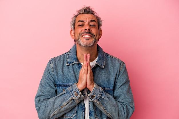Uomo caucasico di mezza età isolato su sfondo rosa tenendosi per mano in preghiera vicino alla bocca, si sente sicuro.