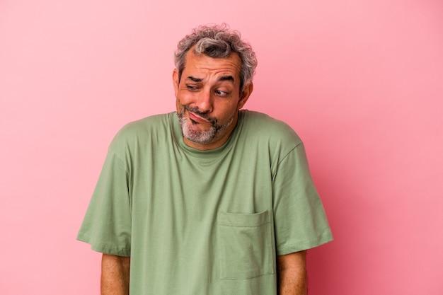 Uomo caucasico di mezza età isolato su sfondo rosa alza le spalle e apre gli occhi confusi.