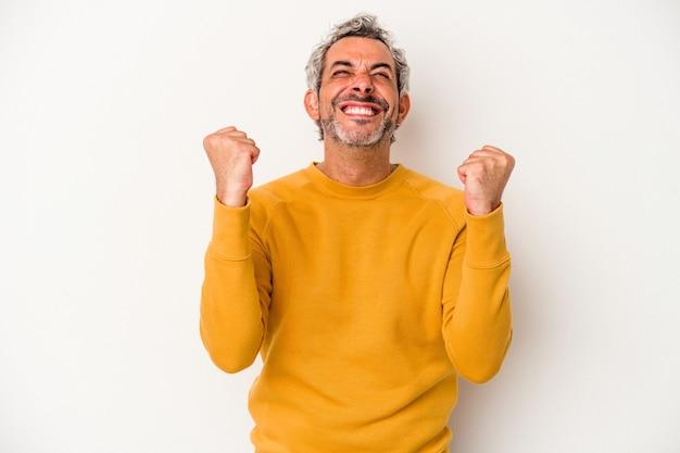 Uomo caucasico di mezza età isolato su sfondo bianco che celebra una vittoria, passione ed entusiasmo, espressione felice.