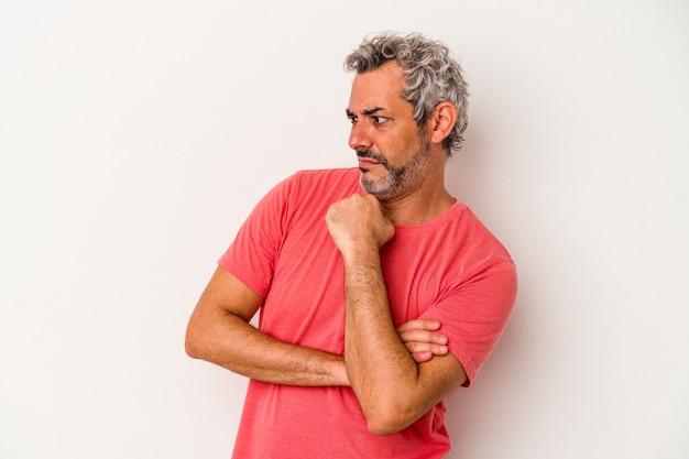 Uomo caucasico di mezza età isolato su sfondo bianco confuso, si sente dubbioso e insicuro.