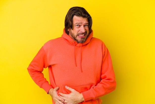 Uomo caucasico di mezza età isolato su sfondo giallo con dolore al fegato, mal di stomaco.