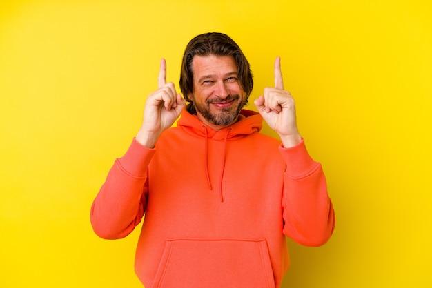 L'uomo caucasico di mezza età isolato su sfondo giallo indica con entrambe le dita anteriori in alto mostrando uno spazio vuoto.