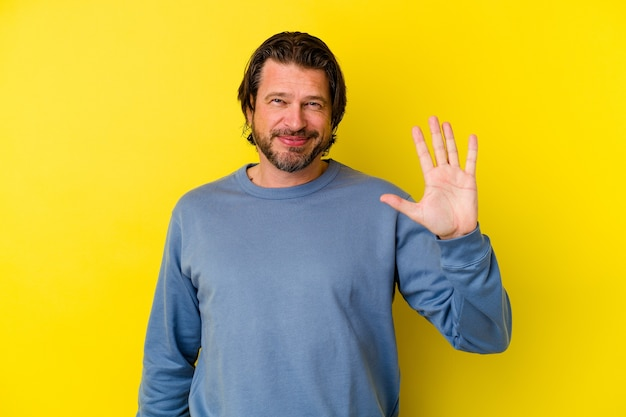 Uomo caucasico di mezza età isolato su sfondo giallo sorridente allegro che mostra il numero cinque con le dita.