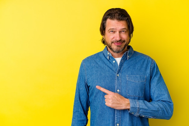 Uomo caucasico di mezza età isolato su sfondo giallo sorridente e rivolto da parte, mostrando qualcosa in uno spazio vuoto.