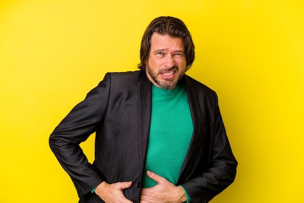 Uomo caucasico di mezza età isolato sulla parete gialla che ha un dolore al fegato, mal di stomaco.