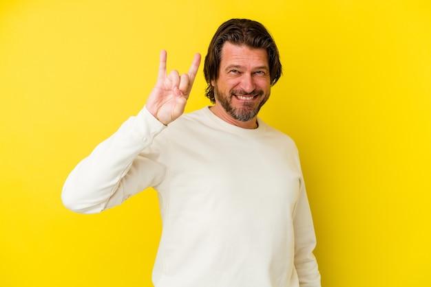 Uomo caucasico di mezza età isolato sulla parete gialla che mostra un gesto di corna come un concetto di rivoluzione.