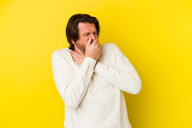 L'uomo caucasico di mezza età in giallo soffre di dolore alla gola a causa di un virus o di un'infezione.