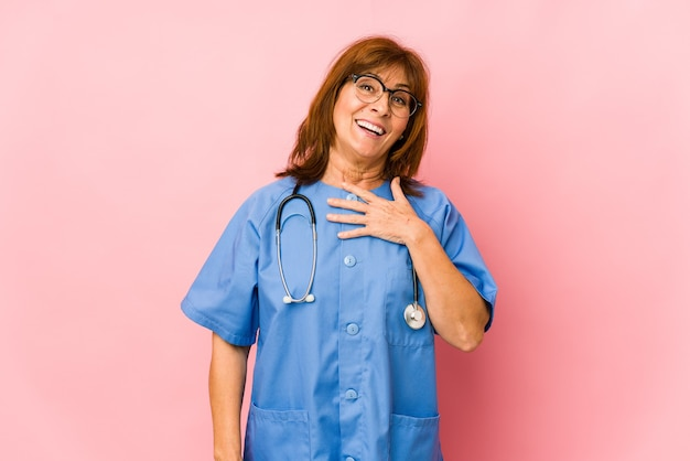 La donna caucasica dell'infermiera di mezza età isolata ride ad alta voce mantenendo la mano sul petto.