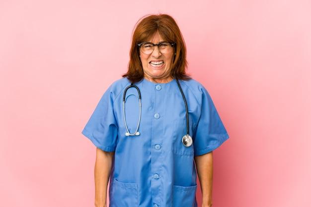 Donna caucasica dell'infermiera di mezza età isolata che grida molto arrabbiata e aggressiva.