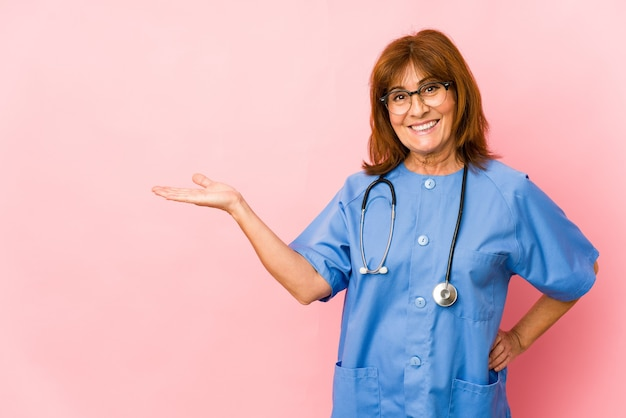 Donna caucasica dell'infermiera di mezza età isolata che mostra uno spazio della copia su una palma e che tiene un'altra mano sulla vita.