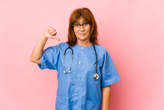 Donna caucasica dell'infermiera di mezza età isolata che mostra un gesto di antipatia, pollici giù. concetto di disaccordo.
