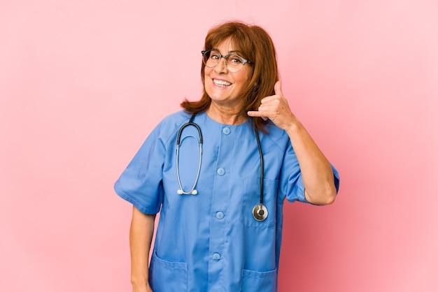 Donna caucasica dell'infermiera di mezza età isolata che mostra un gesto di chiamata di telefono cellulare con le dita.