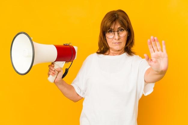 Donna caucasica di mezza età che tiene un megafono in piedi con la mano tesa che mostra il segnale di stop, impedendoti.