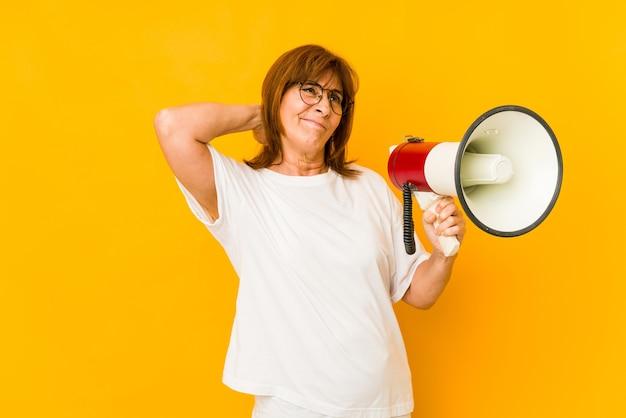 Donna caucasica di mezza età che tiene un megafono che tocca la parte posteriore della testa, pensando e facendo una scelta.