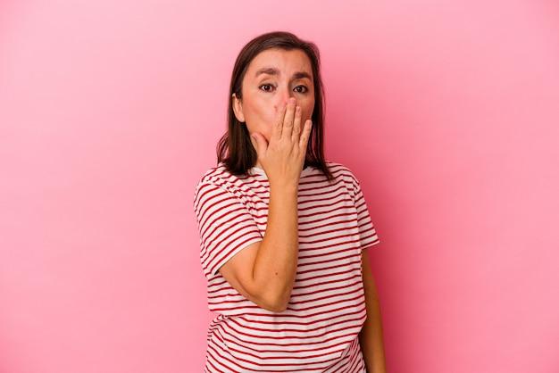 Donna caucasica di mezza età isolata su sfondo rosa scioccata, coprendo la bocca con le mani, ansiosa di scoprire qualcosa di nuovo. Foto Premium