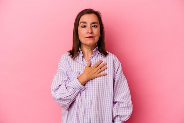 Donna caucasica di mezza età isolata su sfondo rosa prestando giuramento, mettendo la mano sul petto.