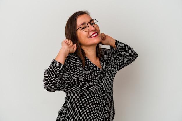 Donna caucasica di mezza età isolata su fondo bianco che allunga le braccia, posizione rilassata.
