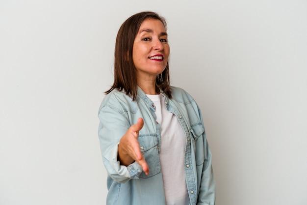 Donna caucasica di mezza età isolata su fondo bianco che allunga la mano alla macchina fotografica nel gesto di saluto.