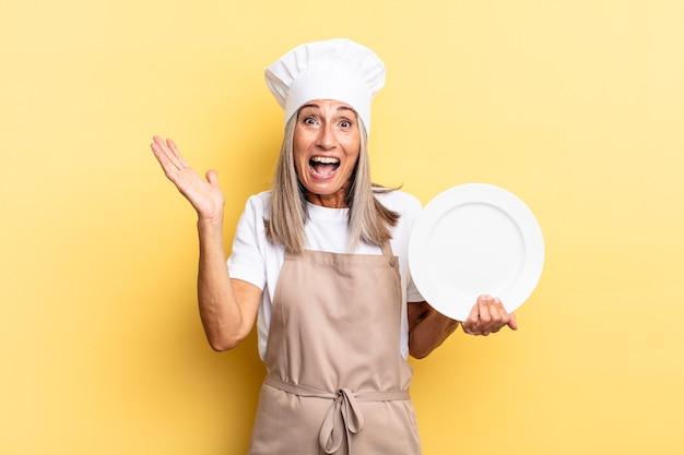 Donna chef di mezza età che si sente felice, eccitata, sorpresa o scioccata, sorridente e stupita per qualcosa di incredibile e con in mano un piatto