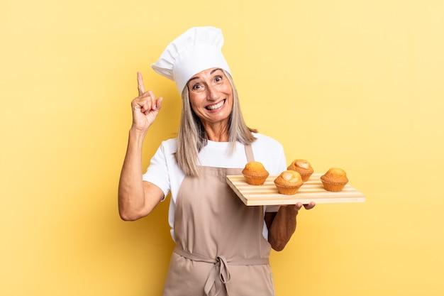 Donna chef di mezza età che si sente un genio felice ed eccitato dopo aver realizzato un'idea, alzando allegramente il dito, eureka! e con in mano un vassoio di muffin