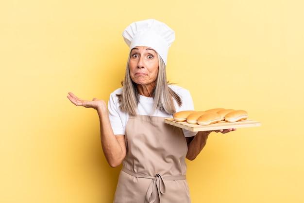 Donna chef di mezza età che si sente perplessa e confusa, dubitando, ponderando o scegliendo diverse opzioni con un'espressione divertente e tenendo in mano un vassoio del pane