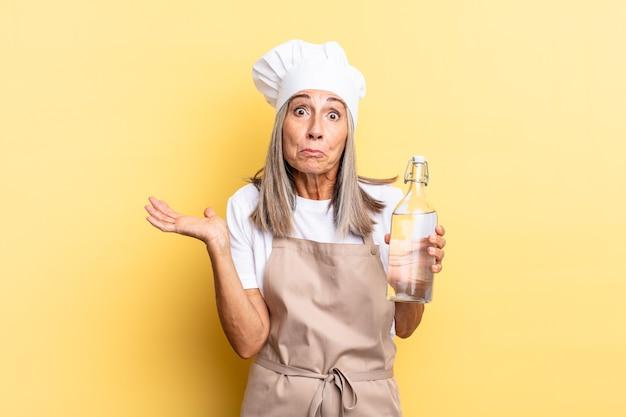 Donna chef di mezza età che si sente perplessa e confusa, dubitando, ponderando o scegliendo diverse opzioni con un'espressione divertente con una bottiglia d'acqua