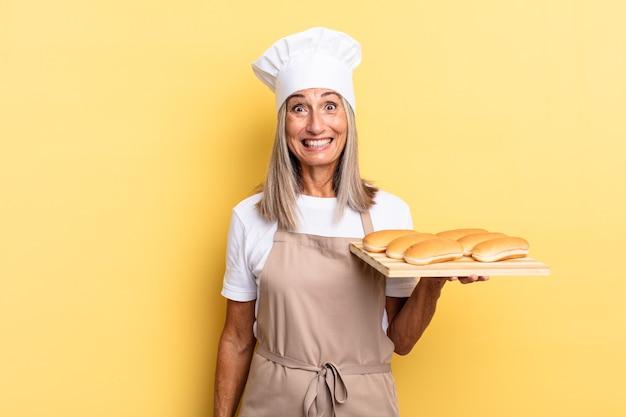 Donna chef di mezza età che sembra felice e piacevolmente sorpresa, eccitata con un'espressione affascinata e scioccata e con in mano un vassoio di pane