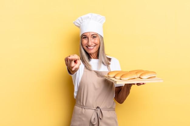 Donna chef di mezza età che punta alla telecamera con un sorriso soddisfatto, fiducioso e amichevole, scegliendo te e tenendo in mano un vassoio di pane