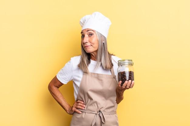 Donna chef di mezza età che scrolla le spalle, si sente confusa e incerta, dubitando con le braccia incrociate e lo sguardo perplesso che tiene i chicchi di caffè