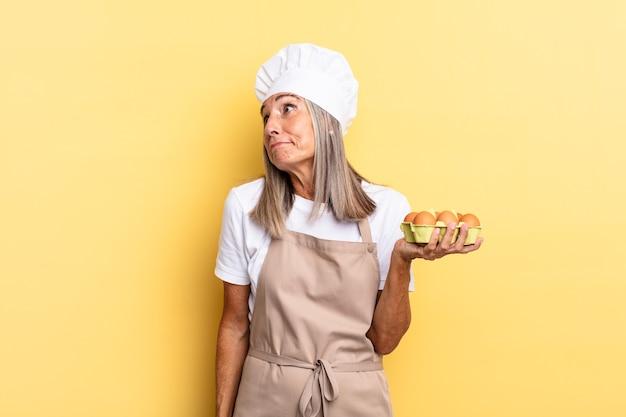 Donna chef di mezza età che scrolla le spalle, si sente confusa e incerta, dubitando con le braccia incrociate e lo sguardo perplesso che tiene in mano una scatola di uova