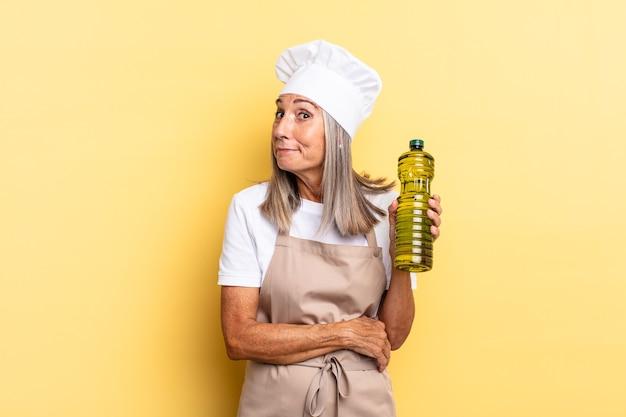 Donna chef di mezza età che scrolla le spalle, si sente confusa e incerta, dubitando con le braccia incrociate e lo sguardo perplesso