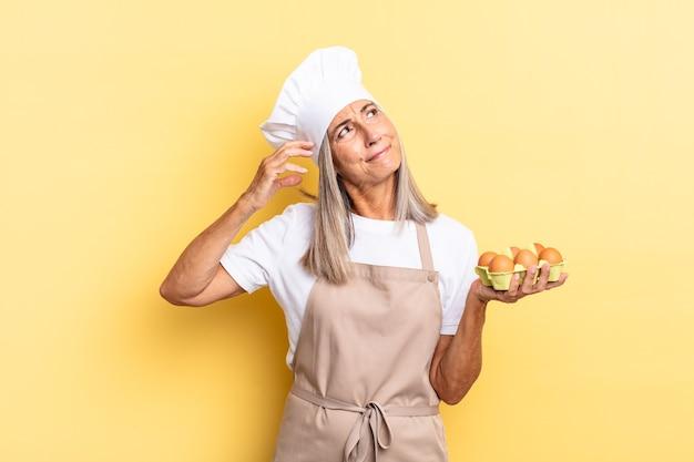 Donna chef di mezza età che sorride felicemente e sogna ad occhi aperti o dubita, guardando di lato con in mano una scatola di uova