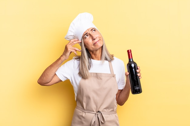 Donna chef di mezza età che sorride felicemente e sogna ad occhi aperti o dubita, guardando di lato con in mano una bottiglia di vino