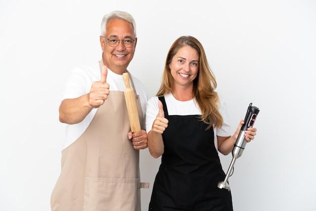 Coppia di chef di mezza età isolata su sfondo bianco che fa un gesto di pollice in alto perché è successo qualcosa di buono