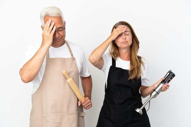 Coppia di chef di mezza età isolata su sfondo bianco con espressione facciale sorpresa e scioccata