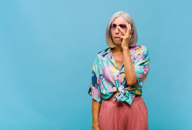 Donna fredda di mezza età che si sente annoiata, frustrata e assonnata dopo un compito noioso, noioso e noioso, tenendo la faccia con la mano