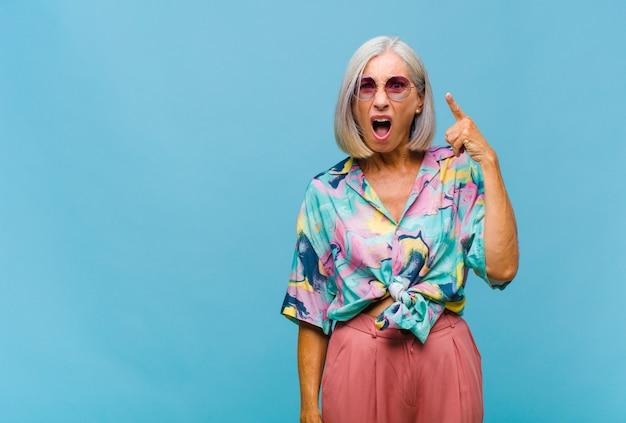 Donna fredda di mezza età che indica alla macchina fotografica con un'espressione aggressiva arrabbiata