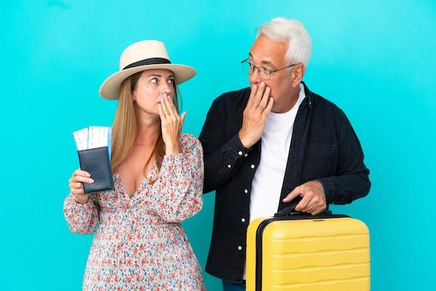 Coppia di mezza età che va in viaggio e tiene in mano una valigia isolata su sfondo blu che copre la bocca con le mani per aver detto qualcosa di inappropriato