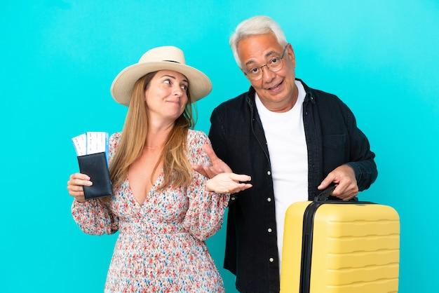 Coppia di mezza età che va in viaggio e tiene in mano una valigia isolata su sfondo blu facendo un gesto non importante mentre solleva le spalle