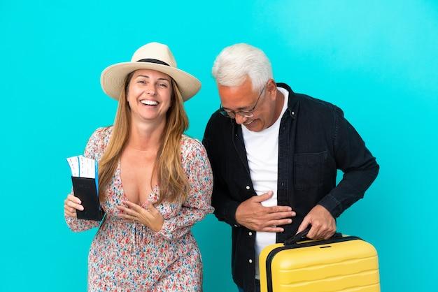 Coppia di mezza età che va in viaggio e tiene in mano una valigia isolata su sfondo blu sorridendo molto mentre mette le mani sul petto